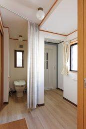 居室横のトイレは扉を付けず、出入りしやすいカーテンに。