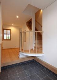 家の顔、玄関で目を引くのは宙に浮くR階段。存在感がありながら圧迫感のないデザイン。