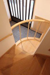階段上部からの眺め。玄関サッシの格子と手摺りの格子が美しい。
